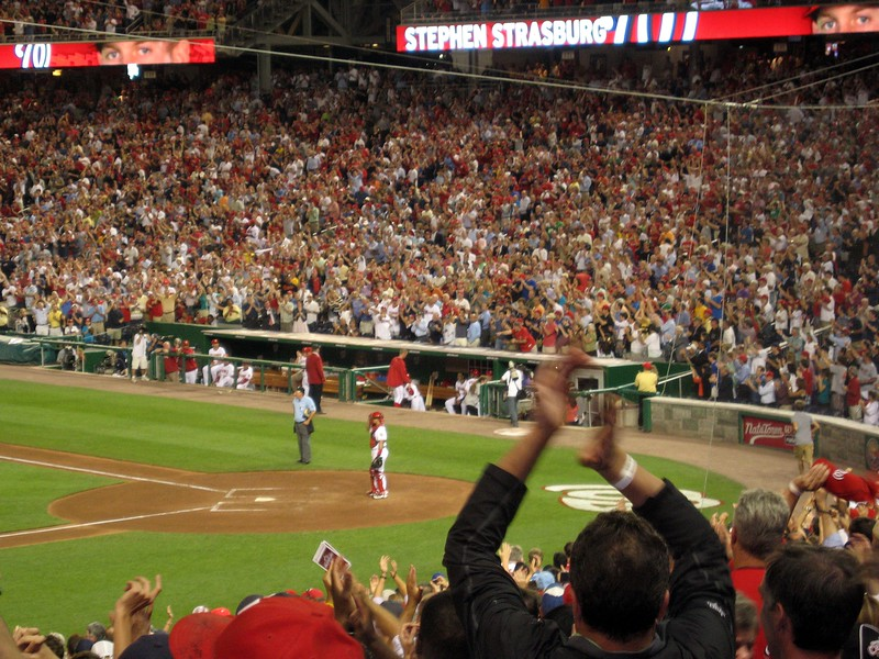 Stephen Strasburg receives a standing ovation as he doffs his cap from the dugout after his record-breaking debut