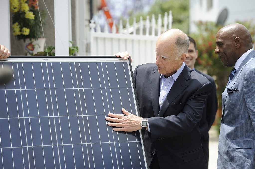 . LONG BEACH, CALIF. USA -- Gov. Jerry Brown checks out a solar panel before speaking at a north Long Beach (Calif.) home during a solar installation on Friday, May 17, 2013. This is the sixth family on this North Long Beach block to be assisted by the Single-family Affordable Solar Homes Program. This installation will allow the homeowners to save up to 90% on their electricity bills. Photo by Jeff Gritchen / Los Angeles Newspaper Group
