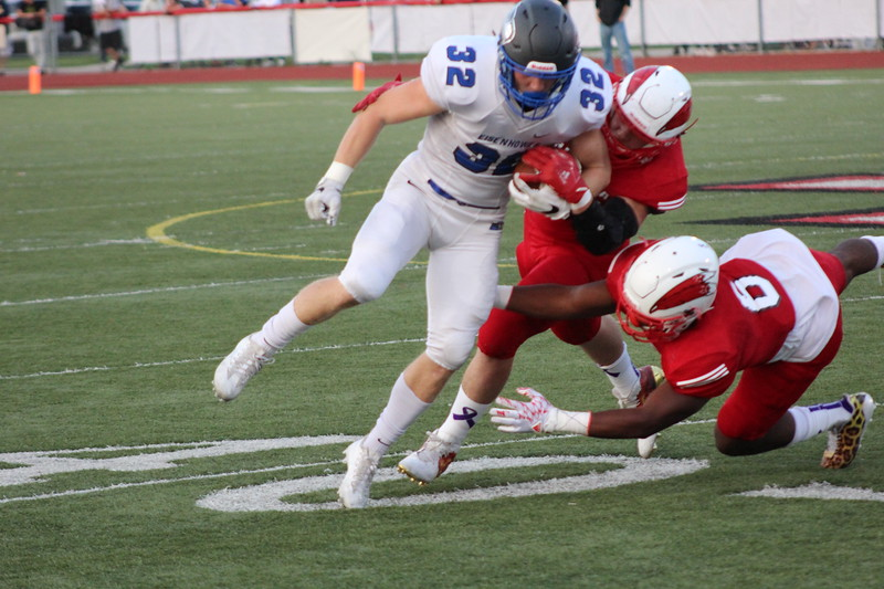 Eisenhower's Caleb Oyster prepares to get tackled by a pair of Chippewa Valley defenders during their MAC Red Division game on Sept. 15, 2017. (Gallery by Kevin Lozon)