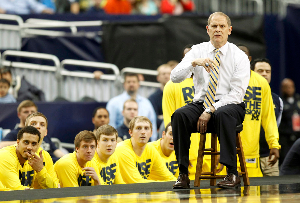 Description of . Michigan Wolverines head coach John Beilein coaches from a stool on the floor in their South Regional NCAA men\'s basketball game against the Florida Gators in Arlington, Texas March 31, 2013. REUTERS/Mike Stone