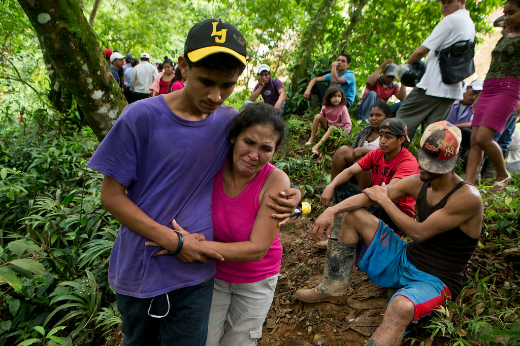 . Margarita Mendez, hugs her son while she cries and waits for news of her other son Salvador Urbina, one of the miners trapped at El Comal gold and silver mine after a landslide trapped at least 24 miners inside, in Bonanza, Nicaragua, Friday, Aug. 29, 2014. Rescuers on Friday located 20 of at least 24 gold miners trapped by a landslide in northern Nicaragua, but were not immediately able to bring them to safety. (AP Photo/Esteban Felix)
