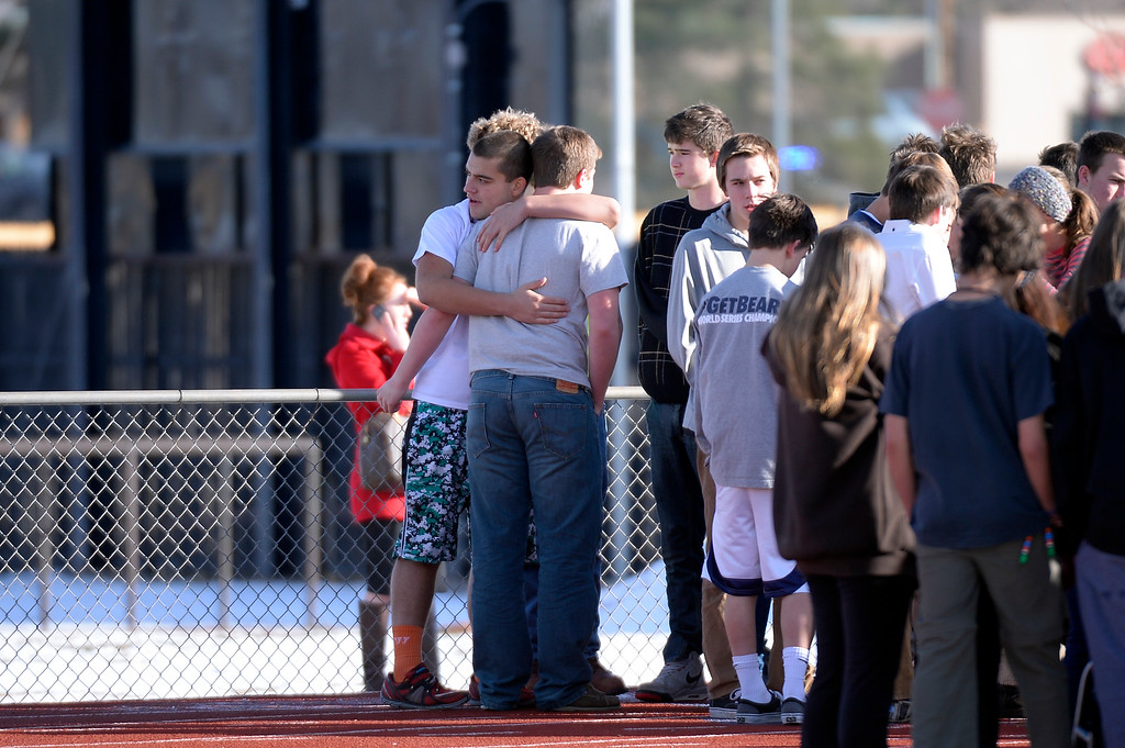 . CENTENNIAL, CO - Students hug as they stand out side on the football field after a gunman was spotted inside Arapahoe High School December 13, 2013. The gunman was targeting a teacher at the school. The gunman shot two students in the process and then turned the gun on himself. (Photo by John Leyba/The Denver Post)