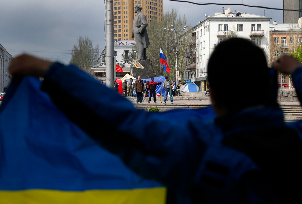 """. A pro Ukrainian supporter, foreground, stands with a Ukrainian flag opposite pro Russian supporters in Donetsk, eastern Ukraine, Tuesday, April 22, 2014. U.S. Vice President Joe Biden warned Russia on Tuesday that \""""it\'s time to stop talking and start acting\"""" to reduce tension in Ukraine. Biden called on Moscow to encourage pro-Russia separatists in eastern Ukraine to vacate government buildings and checkpoints, accept amnesty and \""""address their grievances politically.\"""" (AP Photo/Sergei Grits)"""