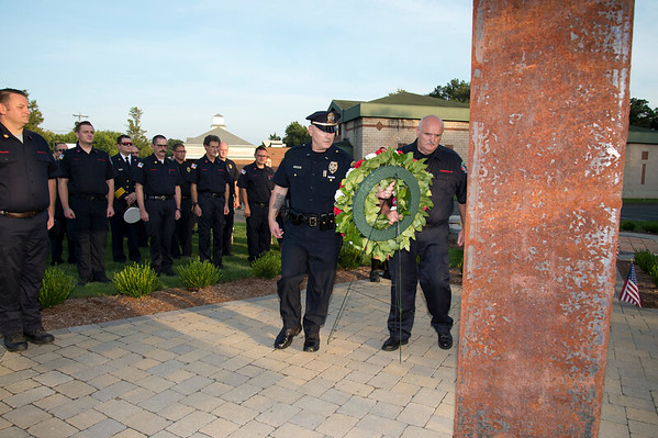 09/11/19 Wesley Bunnell | StaffrrThe Kensington Fire Department held a 9/11 memorial service on Wednesday evening in front of the department at 880 Farmington Ave. Farmington Police Lt. and Kensington fire volunteer Patrick Buckley, L, carries a wreath along with fire Commissioner Tom Powers which is placed in front of steel structural beams from World Trade Center buildings 1 and 2.