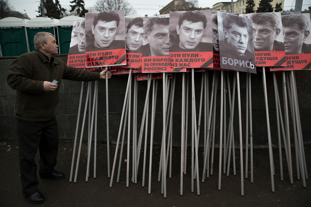 . A man prepares portraits of opposition leader Boris Nemtsov who was gunned down on Friday, Feb. 27, 2015 near the Kremlin, to carry on the march in Moscow, Russia, Sunday, March 1, 2015. Russian investigators, politicians and political commentators on state television on Saturday covered much ground in looking for the reason Nemtsov was gunned down in the heart of Moscow, but they sidestepped one possibility, that he was murdered for his relentless opposition to Putin. The posters read in Russian \'those bullets for everyone of us,  he fought for the freedom of Russia\'. (AP Photo/Pavel Golovkin)