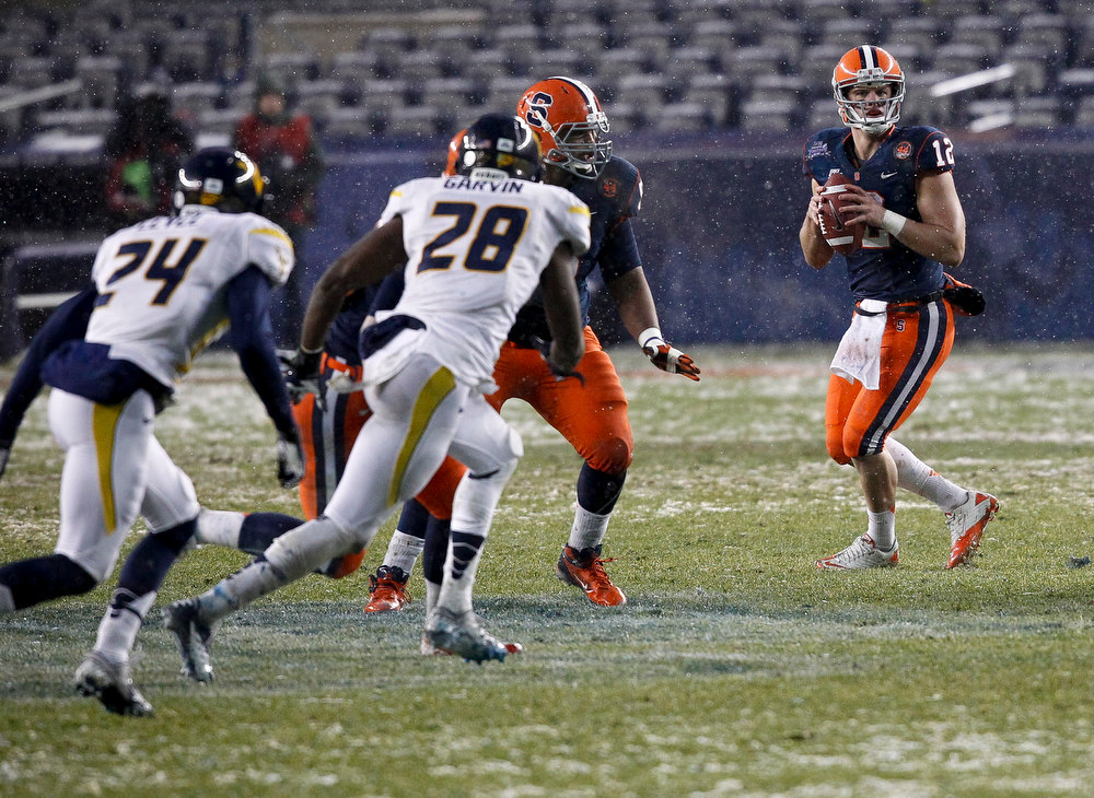 Description of . Ryan Nassib #12 of the Syracuse Orange looks to pass against the West Virginia Mountaineers during the New Era Pinstripe Bowl at Yankee Stadium on December 29, 2012 in the Bronx borough of New York City.  (Photo by Jeff Zelevansky/Getty Images)