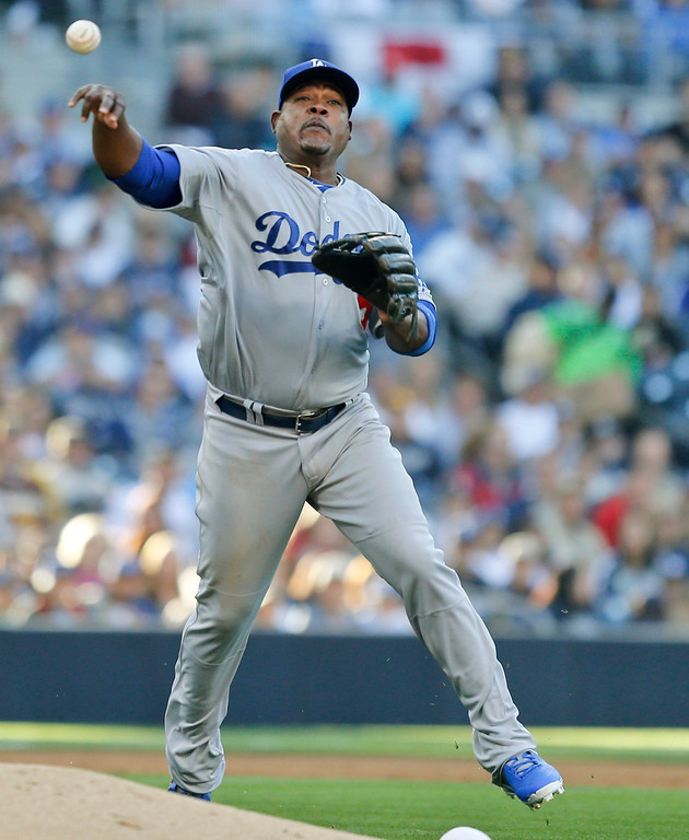 . Los Angeles Dodgers third baseman Juan Uribe makes the running throw to get San Diego Padres\' Chris Denorfia at first in the  third inning of the opening game of Major League baseball in the United States Sunday, March 30, 2014, in San Diego.  (AP Photo/Lenny Ignelzi)