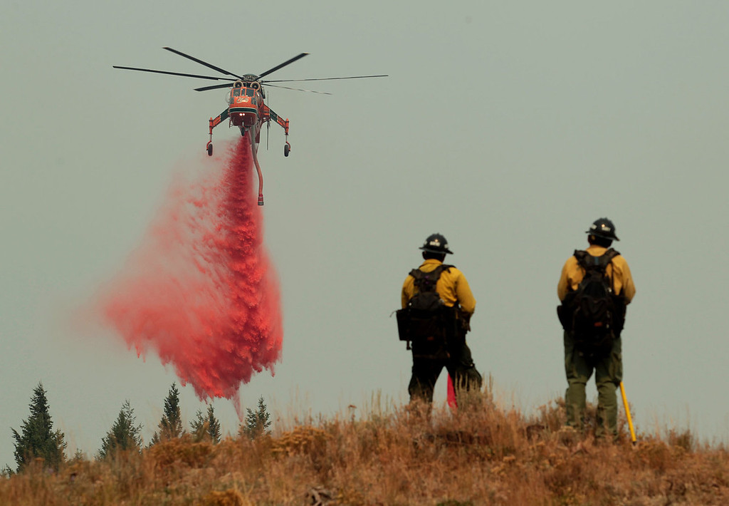 . A helicopter makes a drop on a dozer line around a home to protect it from the Beaver Creek Fire on Sunday, Aug. 18, 2013 outside of Ketchum, Idaho. (AP Photo/Times-News, Ashley Smith)