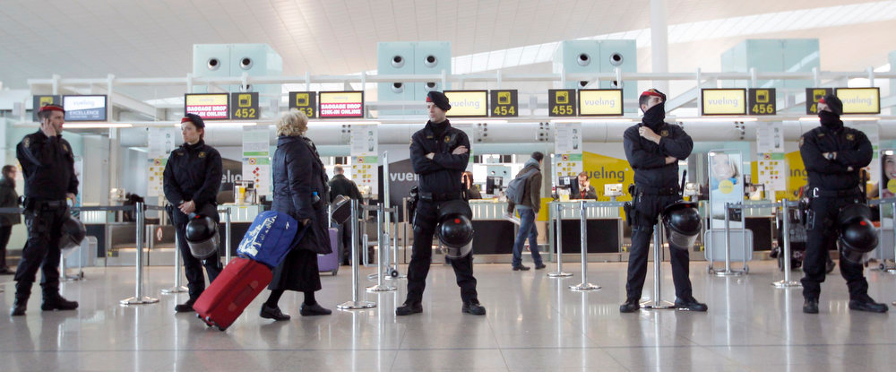 . Riot police officers stand guard at a Vueling check-in desk as a traveller walks past during a protest by Iberia\'s workers at Terminal 1 of Barcelona\'s airport, February 18, 2013. Dozens of Iberia flights were canceled on Monday as workers at the loss-making Spanish flag carrier began a five-day strike over job cuts that is expected to cost the airline and struggling national economy millions of euros in lost business.  REUTERS/Albert Gea