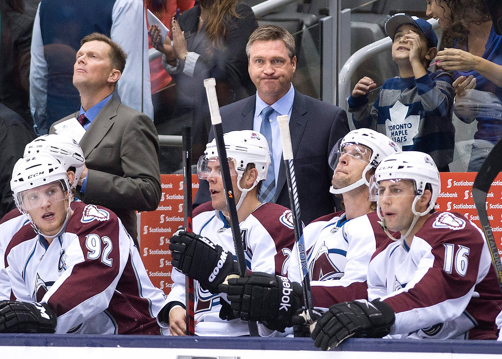. Colorado Avalanche coach Patrick Roy, center, stands behind players during the second period of an NHL hockey game against the Toronto Maple Leafs  in Toronto on Tuesday, Oct. 8, 2013. (AP Photo/The Canadian Press, Nathan Denette)