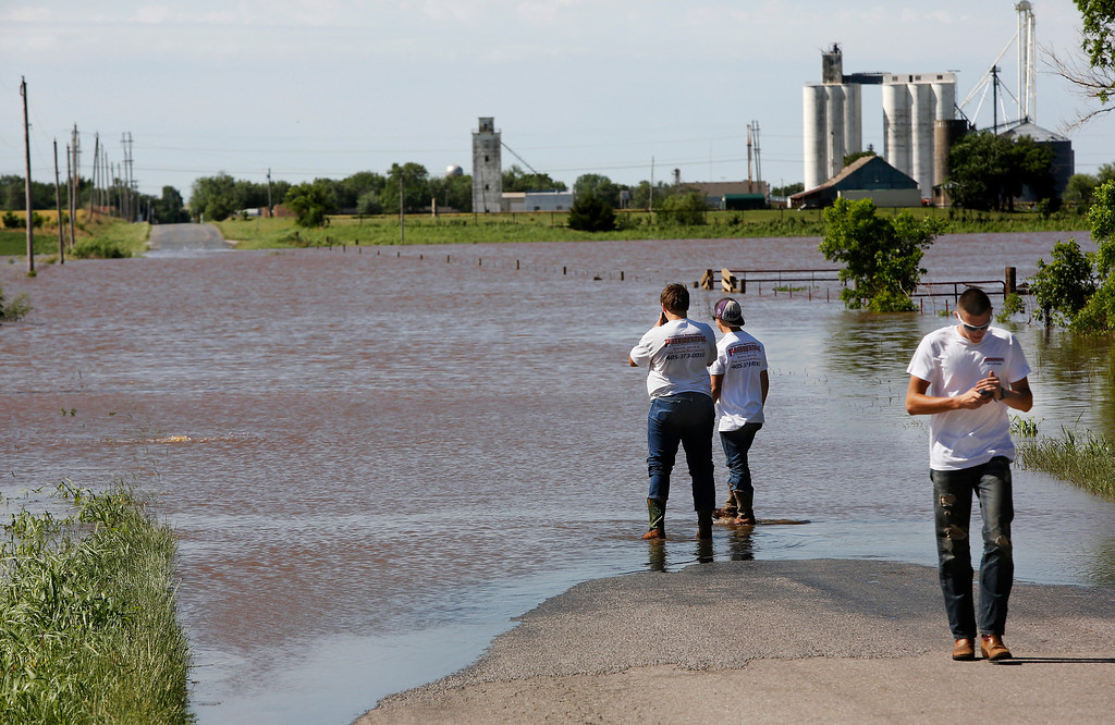 . Matt Wyatt and Chase Biggs check the level of water flowing across Banner Road in El Reno, Okla as their friend, Tyler Eisenhour determines it is too deep and walks to their truck to find an alternate route to their work site on  Saturday, June 1, 2013.  (AP Photo/The Oklahoman, Jim Beckel)