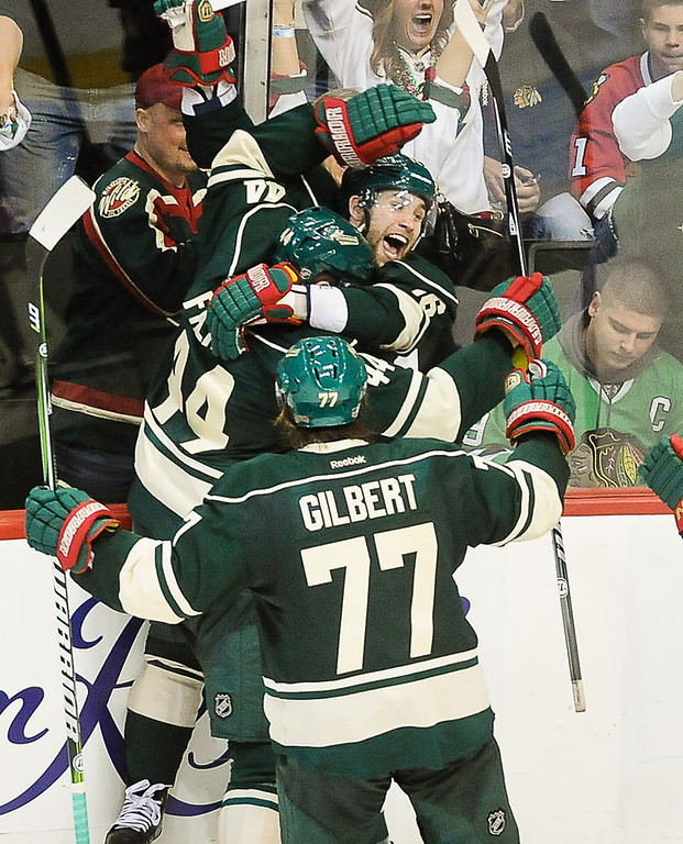 . Wild players swarm Jason Zucker after he scored the winning goal in overtime as Minnesota beat the Chicago Blackhawks, 3-2,  in Game 3 of their Western Conference quarterfinal series at Xcel Energy Center in St. Paul on Sunday, May 5, 2013.  (Pioneer Press: Ben Garvin)