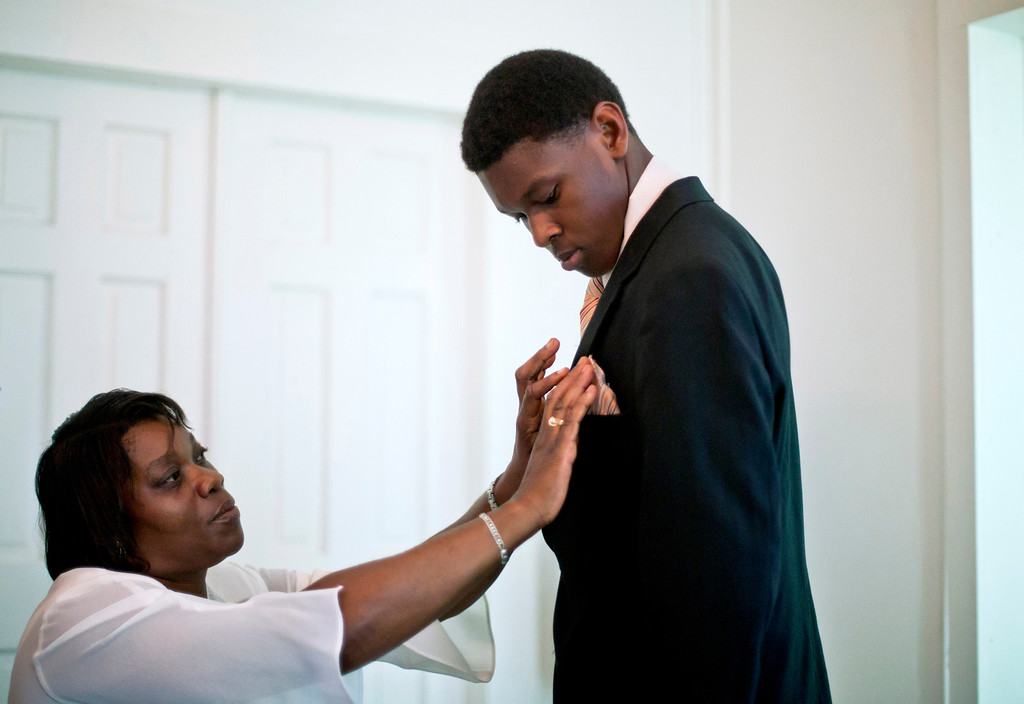 . Mary Bailey, left, puts a handkerchief in the suit pocket of her cousin, Marvin Grovner, 16, as they attend a church service for the 129th anniversary of St. Luke Baptist Church on Sapelo Island, Ga. on Sunday, June 9, 2013. Grovner is one of 47 residents, most of them descendants of West African slaves known as Geechee, who remain on Sapelo Island, the coastal Georgia island where their ancestors were brought to work a plantation in the early 1800s. Isolated over time to the Southeast\'s barrier islands, the Geechee of Georgia and Florida, otherwise known as Gullah in the Carolinas, have retained their African traditions more than other African American communities in the U.S. Once freed, the slaves were able to acquire land and created settlements on the island, of which only the tiny 464-acre Hog Hammock community still exists. Residents say a sudden tax hike, lack of jobs, and development is endangering one of the last remaining Geechee communities from Florida to North Carolina. (AP Photo/David Goldman)