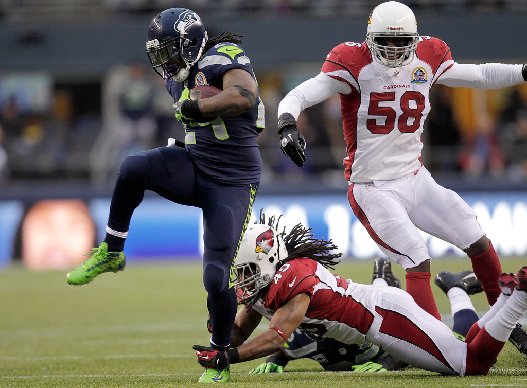 . Seattle Seahawks running back Marshawn Lynch (24) runs for a 33-yard touchdown past Arizona Cardinals strong safety Rashad Johnson (49) and inside linebacker Daryl Washington (58) during the third quarterof an NFL football game in Seattle, Sunday, Dec. 9, 2012. (AP Photo/Stephen Brashear)