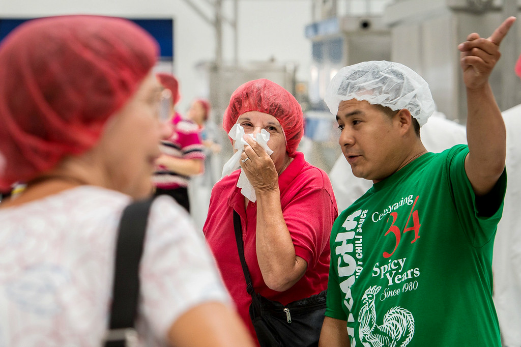 . Munci Gunner, of San Marino, center, covers her nose as she tours the Sriracha hot sauce factory to see the chili grinding process at Huy Fong Foods in Irwindale on Friday, August 22, 2014. (Photo by Watchara Phomicinda/ Pasadena Star-News)