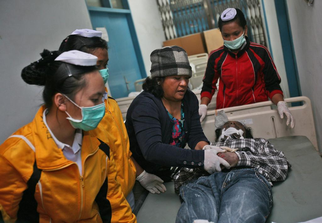 . Nurses dress a victim of the eruption of Mount Sinabung for burial at a hospital in Kabanjahe, North Sumatra, Indonesia, Saturday, Feb. 1, 2014.  (AP Photo/Binsar Bakkara)