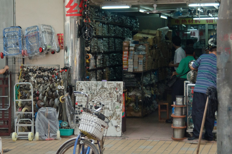 The first of many shop stall photos - many shops selling the same things right next to each other...a hardware block, then a group of fan shops, then plumbing, etc.  This guy sold hardware - items he has are on the boards in front.
