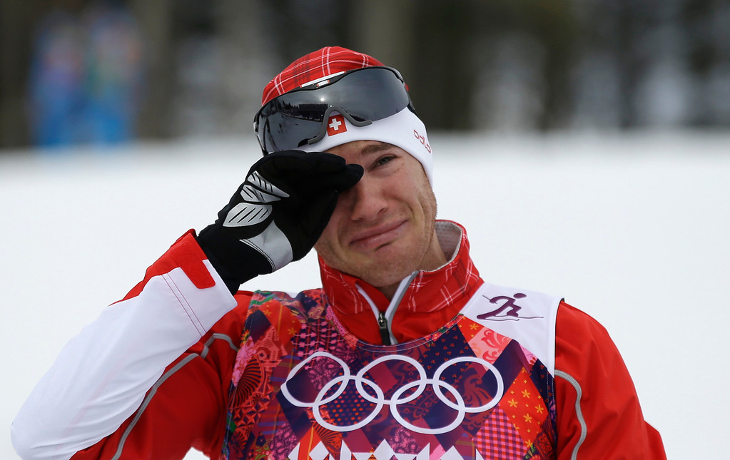 . Switzerland\'s Dario Cologna cries on the podium after winning the gold during the men\'s cross-country 30k skiathlon at the 2014 Winter Olympics, Sunday, Feb. 9, 2014, in Krasnaya Polyana, Russia. (AP Photo/Gregorio Borgia)