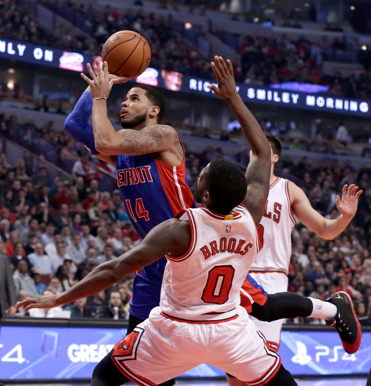 . Detroit Pistons guard D.J. Augustin (14) shoots past Chicago Bulls guard Aaron Brooks, during the first half of an NBA basketball game Monday, Nov. 10, 2014, in Chicago. (AP Photo/Charles Rex Arbogast)