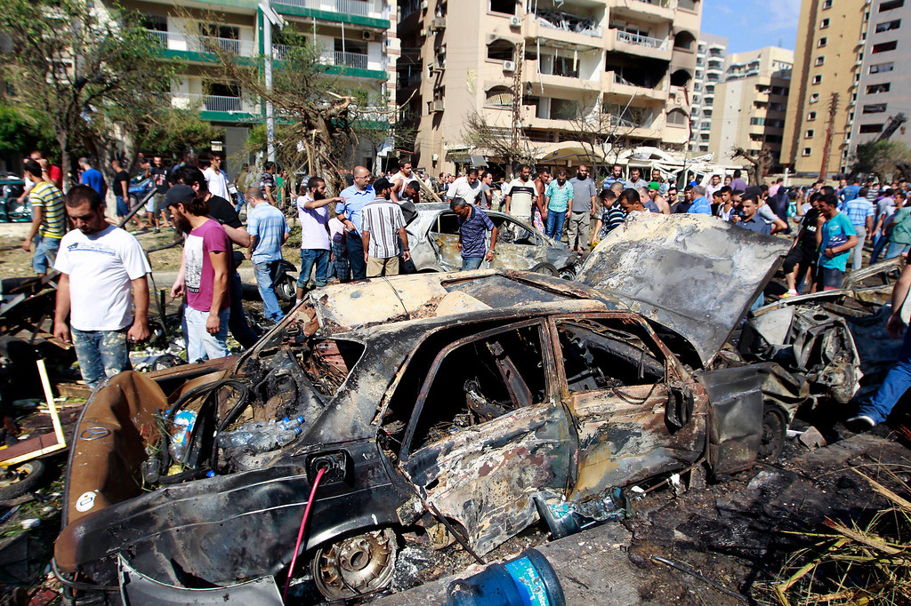 . People gather outside of the Salam mosque amid charred cars and wide damage, in the northern city of Tripoli, Lebanon, Friday, Aug. 23, 2013. (AP Photo/Bilal Hussein)