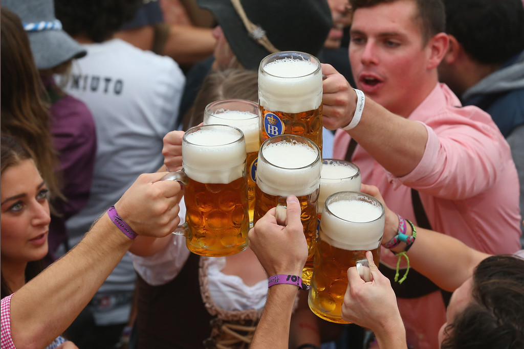 . Revellers enjoy the first beer at the opening day of the Oktoberfest at Hofbraeu tent on September 21, 2013 in Munich, Germany. The Munich Oktoberfest, which this year will run from September 21 through October 6, is the world\'s largest beer fest and draws millions of visitors.  (Photo by Alexander Hassenstein/Getty Images)