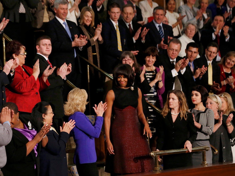 Description of . U.S. first lady Michelle Obama (C) is applauded by attendees, including  Dr. Jill Biden (3rd from L, in blue), wife of Vice President Joe Biden, as she arrives for U.S. President Barack Obama's State of the Union speech on Capitol Hill in Washington, February 12, 2013. REUTERS/Jason Reed