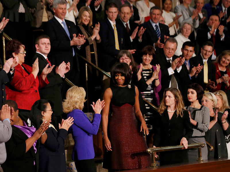 . U.S. first lady Michelle Obama (C) is applauded by attendees, including  Dr. Jill Biden (3rd from L, in blue), wife of Vice President Joe Biden, as she arrives for U.S. President Barack Obama\'s State of the Union speech on Capitol Hill in Washington, February 12, 2013. REUTERS/Jason Reed