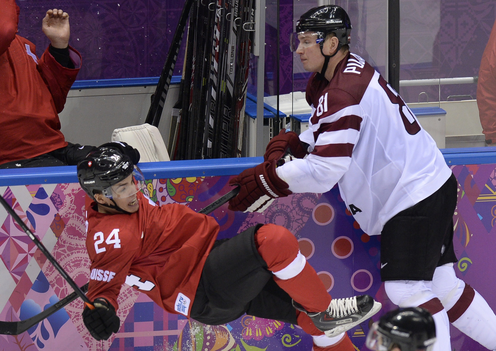 . Latvia\'s Georgijs Pujacs (R) sends Switzerland\'s Reto Suri down on ice during the Men\'s Ice Hockey Play-offs Switzerland vs Latvia at the Bolshoy Ice Dome during the Sochi Winter Olympics on February 18, 2014.  (ALEXANDER NEMENOV/AFP/Getty Images)