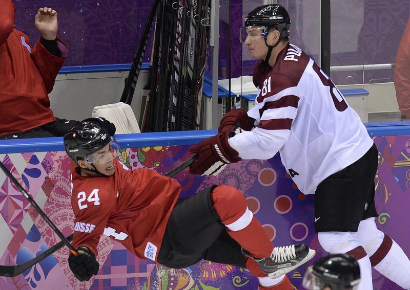 . Latvia\'s Georgijs Pujacs (R) sends Switzerland\'s Reto Suri down on ice during the Men\'s Ice Hockey Play-offs Switzerland vs Latvia at the Bolshoy Ice Dome during the Sochi Winter Olympics on February 18, 2014.  (ALEXANDER NEMENOV/AFP/Getty Images)