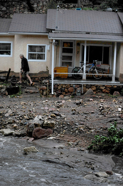 . A man walks around his home after being trapped by flood waters that flowed, Friday, Aug. 9, 2013 in Manitou, Colo. A mudslide has closed U.S. 24 between Cascade and Manitou Springs, and flash flooding in Manitou Springs is stranding vehicles in high, fast-moving water. (AP Photo/The Colorado Springs Gazette, Michael Ciaglo)
