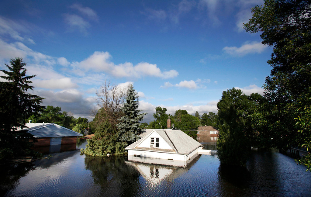 . In this June 27, 2011 file photo, floodwaters from the Souris River surround homes near Minot State University in Minot, N.D. (AP Photo/Charles Rex Arbogast)