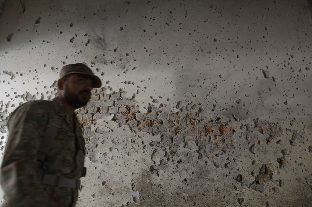 . A Pakistani army soldier walks past a bullet-riddled wall at an army-run school a day after an attack by Taliban militants in Peshawar on December 17, 2014.  Pakistan began three days of mourning on December 17 for the 132 schoolchildren and nine staff killed by the Taliban in the country\'s deadliest ever terror attack as the world united in a chorus of revulsion.  AFP PHOTO / FAROOQ NAEEM/AFP/Getty Images