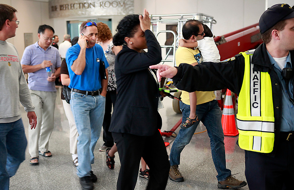 . A woman holds her head as a group of people are escorted from the Reflection Room at San Francisco International Airport where officials were helping passengers aboard the Asiana Airlines Flight 214 that crashed during landing Saturday afternoon July 6, 2013.  (Karl Mondon/Bay Area News Group)