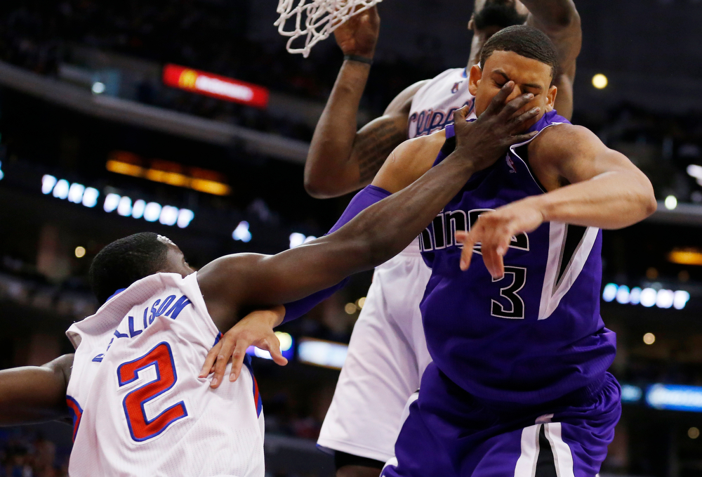 . Sacramento Kings guard Ray McCallum, right, takes a hand to the face from Los Angeles Clippers guard Darren Collison, left, during the second half of an NBA basketball game in Los Angeles, Saturday, April 12, 2014. The Clippers won 117-101. (AP Photo/Danny Moloshok)