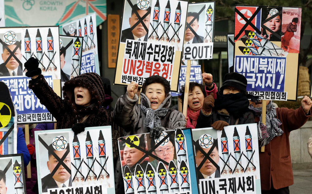 ". South Korean protesters shout slogans during an anti-North Korea rally following a report of the nuclear test conducted by North Korea, in Seoul, South Korea, Tuesday, Feb. 12, 2013. North Korea apparently conducted a widely anticipated nuclear test Tuesday, strongly indicated by an ""explosion-like\"" earthquake that monitoring agencies around the globe said appeared to be unnatural. The letters read \"" Support, U.N. sanction strongly and Out, Kim Jong Un.\"" (AP Photo/Lee Jin-man)"