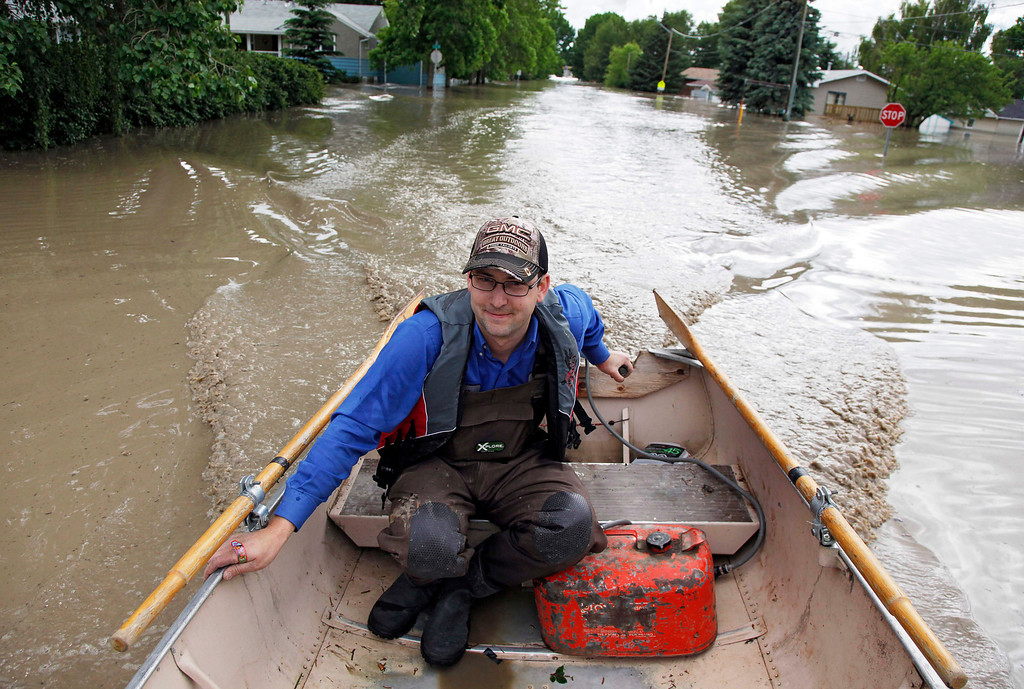 . Roger Poirier pilots a boat along a residential street after gathering belongings from his flooded house in High River, Alta., Thursday, June 20, 2013. Calgary city officials say as many as 100,000 people could be forced from their homes due to heavy flooding in western Canada, while mudslides have forced the closure of the Trans-Canada Highway around the mountain resort towns of Banff and Canmore. (AP Photo/The Canadian Press, Jeff McIntosh )