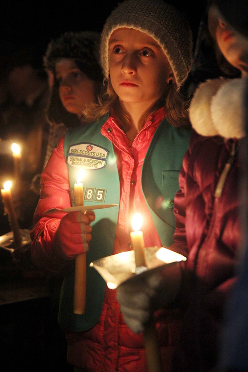 . Lunenburg Girl scout Emily Lavin, 9, with troop 1185 holds a candle at the ceremony in support of Isaac Phillips at the town gazebo on Sunday night. SENTINEL & ENTERPRISE/ JOHN LOVE