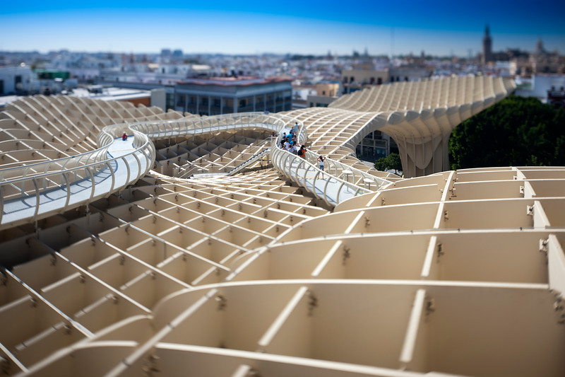 People on the walkway on the top of Metropol Parasol structure, Seville, Spain. Tilted lens used for shallower depth of field.