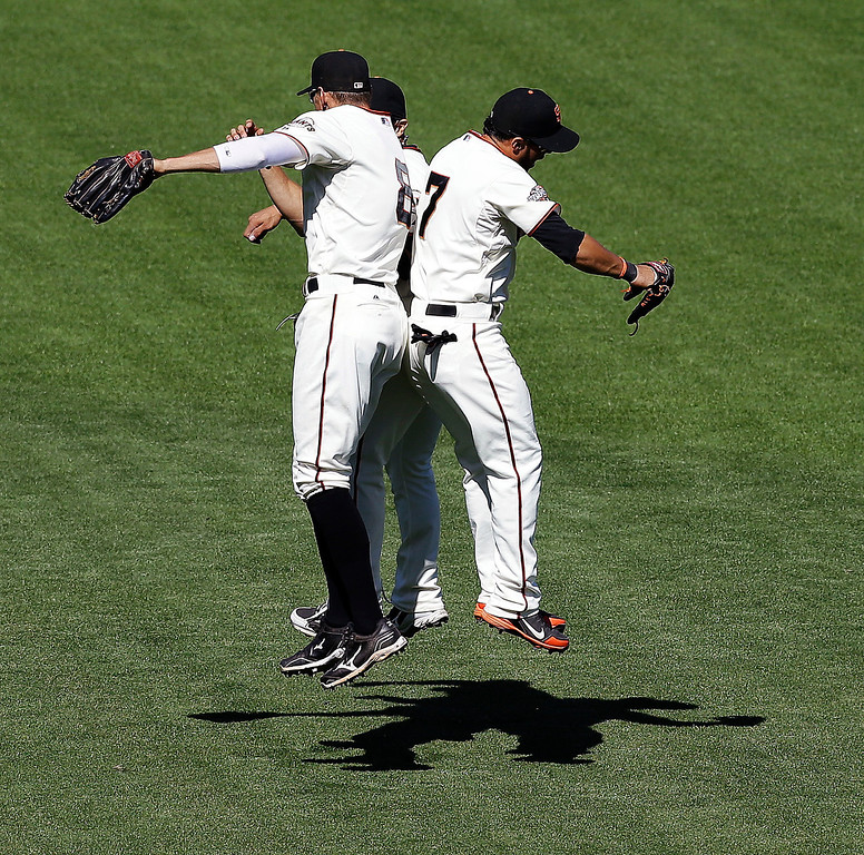 . San Francisco Giants outfielders Hunter Pence, left, Gregor Blanco (7) and Andres Torres, obscured, celebrate their 10-0 win over the Colorado Rockies in a baseball game in San Francisco, Wednesday, April 10, 2013. (AP Photo/Jeff Chiu)