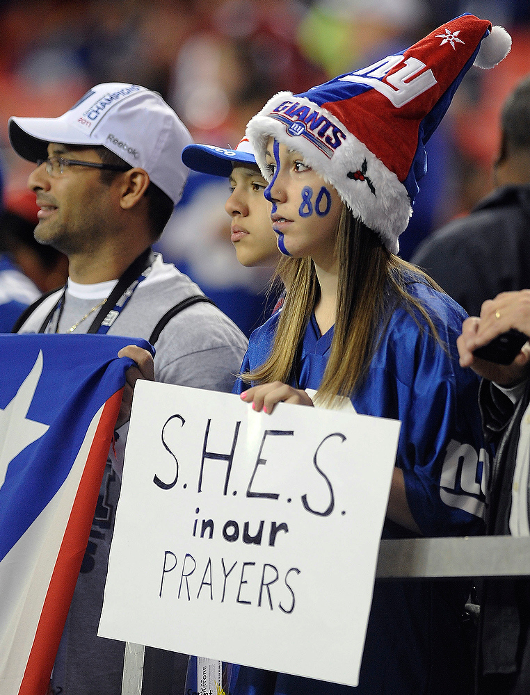 . Makayla Ferfecki, of Kentucky, holds a sign honoring the victims of the shooting at Sandy Hook Elementary School in Newtown, Conn., before the first half of an NFL football game between the Atlanta Falcons and the New York Giants, Sunday, Dec. 16, 2012, in Atlanta. A gunman walked into the school Friday and opened fire, killing 26 people, including 20 children. (AP Photo/Mike Stewart)
