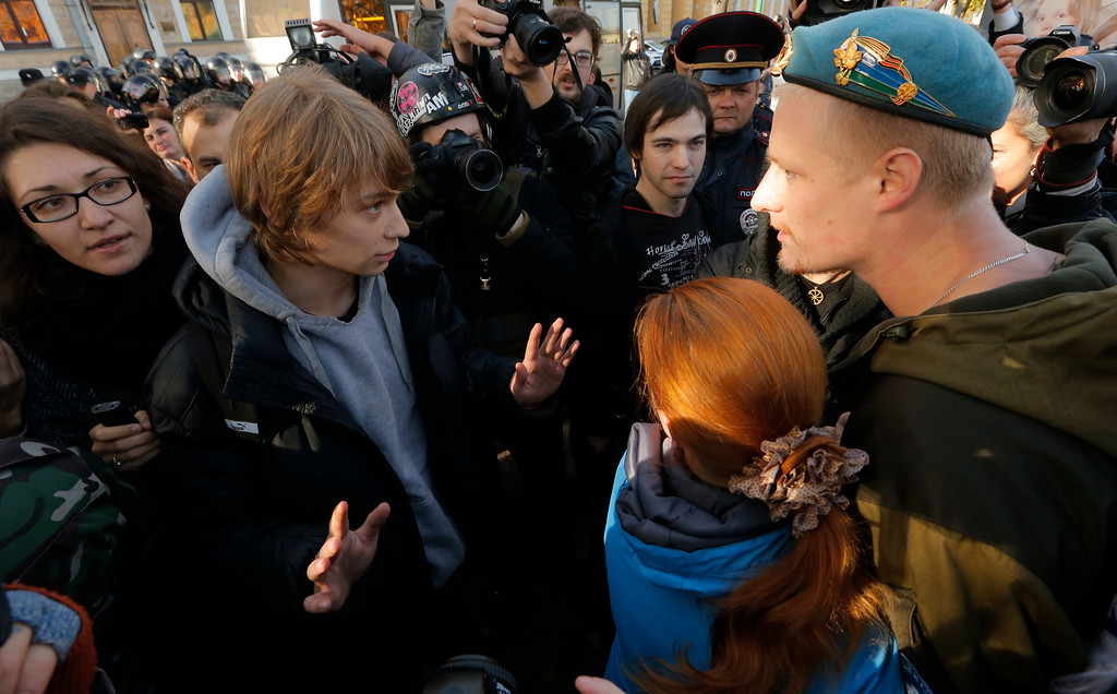 . A gay rights activist, left, argues with anti-gay protesters during an authorized gay rights rally in St.Petersburg, Russia, Saturday, Oct. 12, 2013. A gay rights rally in St. Petersburg has ended in scuffles after several dozen protesters were confronted by about 200 conservative and religious activists. The police standing nearby waited until clashes broke out between the two groups before intervening. According to Russian news agencies, the police detained 67 people from both sides. (AP Photo / Dmitry Lovetsky)