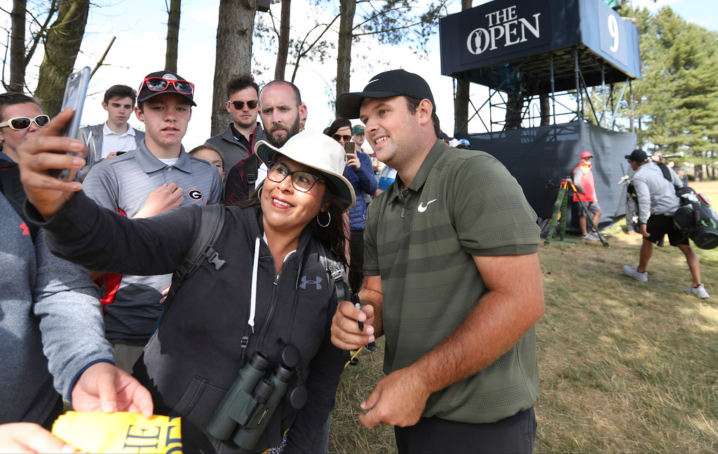 . Patrick Reed of the US has a photograph taken with a fan during a practice round ahead of the British Open Golf Championship in Carnoustie, Scotland, Wednesday July 18, 2018. (AP Photo/Jon Super)