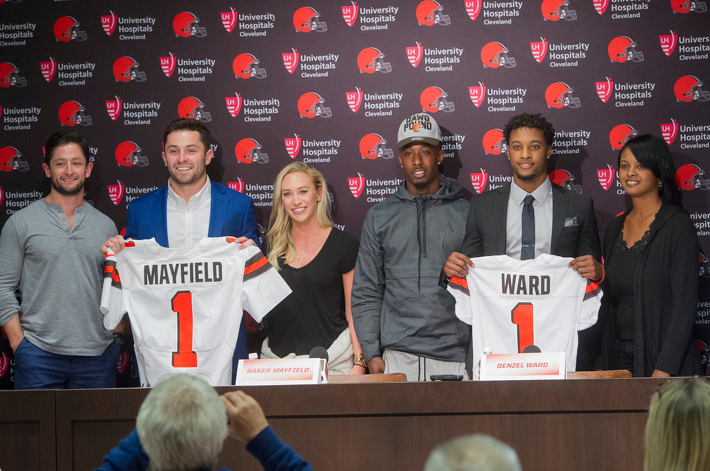 . Cleveland Browns first-round pick Baker Mayfield, second from left, stands with his brother Matt Mayfield, left, and girlfriend, Emily Wilkinson along with fellow first-round pick Denzel Ward, second from right, with his brother Paul Ward III and his mother, Nicole Ward, far right, after a news conference at the Browns headquarters in Berea, Ohio, Friday, April 27, 2018. Mayfield was the first selection in the draft, Ward the fourth. (AP Photo/Phil Long)