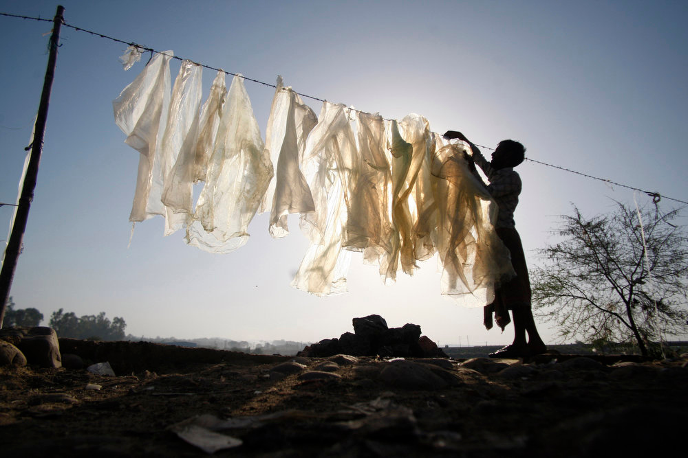 . An Indian man dries plastic bags for reuse at an industrial area on the outskirts of Jammu, India, Wednesday, June 5, 2013. The World Environment Day is celebrated June 5 every year by the United Nations to stimulate global awareness on environmental issues. (AP Photo/Channi Anand)