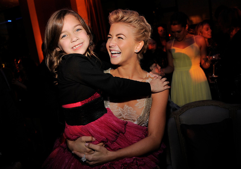 """. Julianne Hough, a cast member in \""""Safe Haven,\"""" lifts up fellow cast member Mimi Kirkland at the post-premiere party for the film, Tuesday, Feb. 5, 2013, in the Hollywood section of Los Angeles. (Photo by Chris Pizzello/Invision/AP)"""