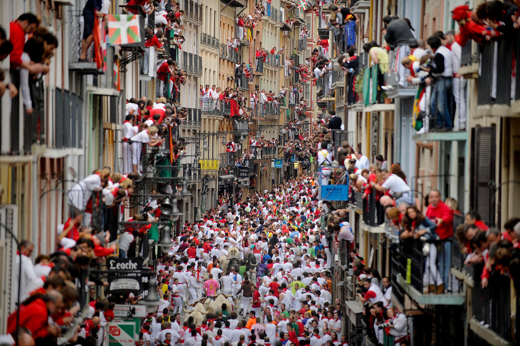 . Participants run in front of Fuente Ymbro\'s bulls during the fifth San Fermin Festival bull run, on July 11, 2012, in Pamplona, northern Spain. The festival is a symbol of Spanish culture that attracts thousands of tourists to watch the bull runs despite heavy condemnation from animal rights groups. (PEDRO ARMESTRE/AFP/GettyImages)