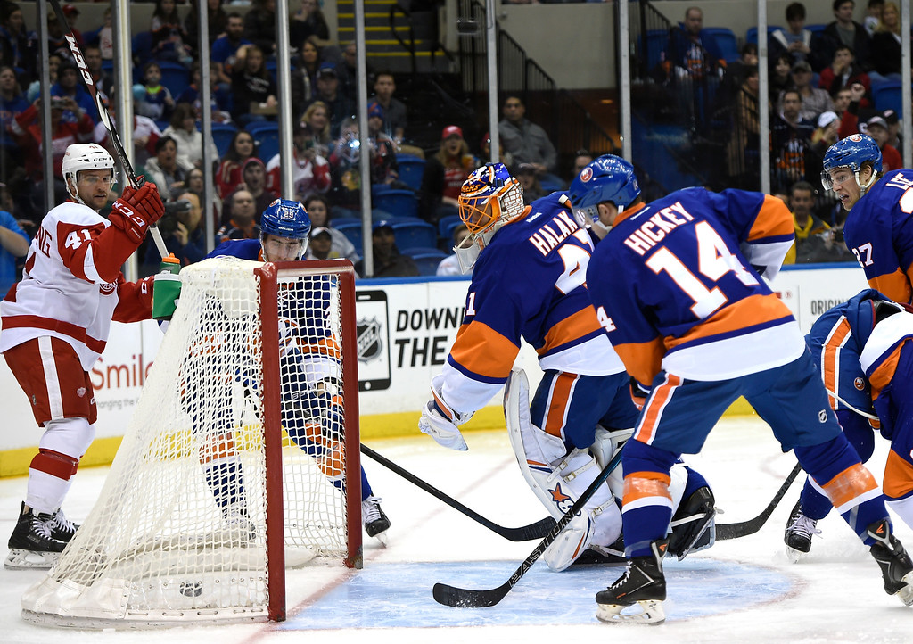 . Detroit Red Wings right wing Luke Glendening, left, New York Islanders goalie Jaroslav Halak, center, and defenseman Thomas Hickey (14) look toward the puck shot by Red Wings left wing Drew Miller (not shown) that scored a goal in the first period of an NHL hockey game on Sunday, March 29, 2015, in Uniondale, N.Y. (AP Photo/Kathy Kmonicek)