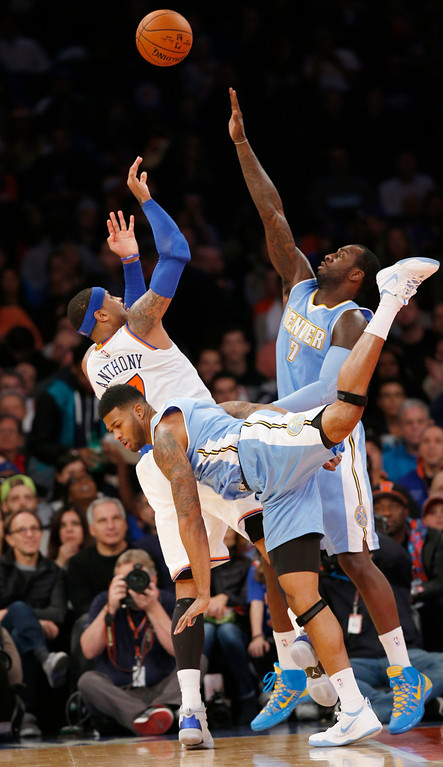 . New York Knicks forward Carmelo Anthony (7) shoots over Denver Nuggets center J.J. Hickson (7) as Nuggets forward Alonzo Gee (1) trips on him in the first half of an NBA basketball game in New York, Sunday, Nov. 16, 2014. (AP Photo/Kathy Willens)