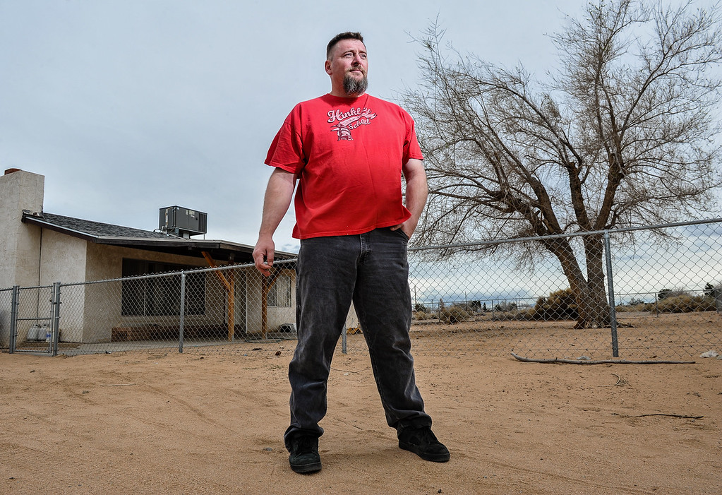. Resident Richard Johnson, 39, who is a member of the town\'s Community Advisory Committee, stands in front of his home in Hinkley, Calif. on Thursday, March 7, 2013. A disabled and unemployed veteran, Johnson is living rent-free in his grandmother\'s home, but will soon be evicted after his grandmother agreed to PG&E\'s buyout program. (Rachel Luna / San Bernardino Sun)