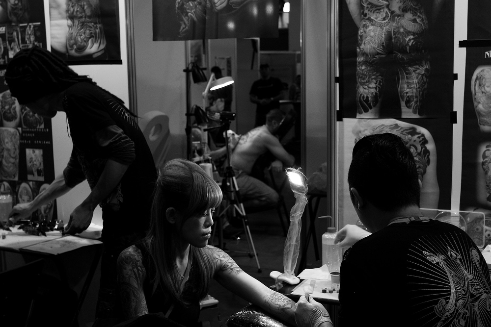 . Tattoo artists from \'Night Action Tattoo\' in Taiwan work on clients during The Australian Tattoo & Body Art Expo at the Royal Hall of Industries, Moore Park on March 8, 2013 in Sydney, Australia. The annual three day event showcases some of Australia\'s best tattoo and body artists and is open to enthusiasts March 8-10.  (Photo by Lisa Maree Williams/Getty Images)